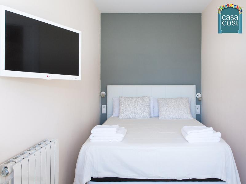 The sunny room with flat screen TV and bedding chosen for its comfort.