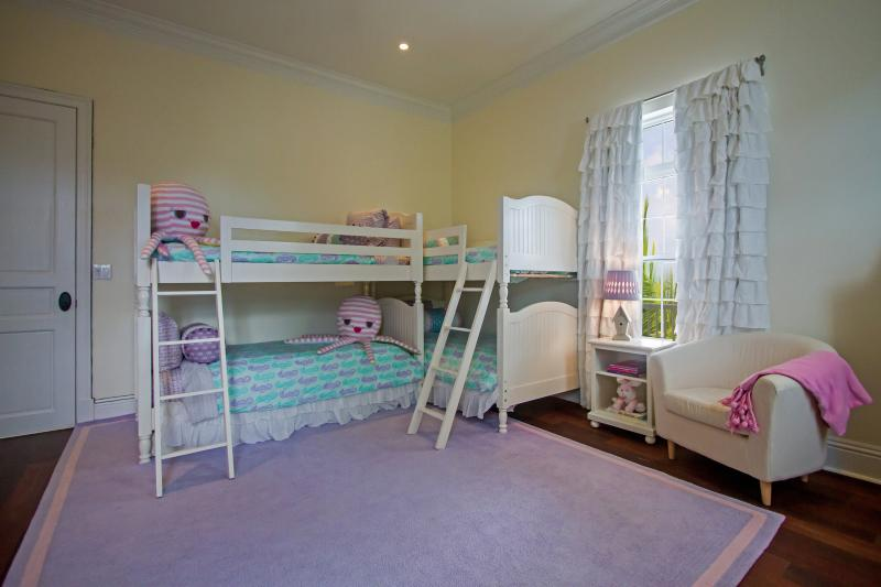 The fun bunk bedroom, with 4 beds and a huge soft rug perfect for reading bed time stories on.