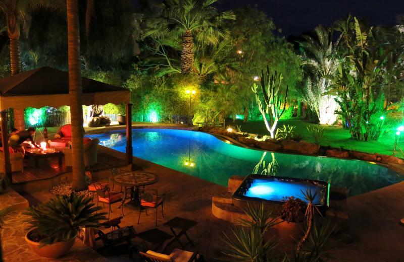 Splendida illuminazione notturna intorno piscina e giardino