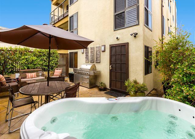 Private patio with hot tub, outdoor seating, and lounge chairs