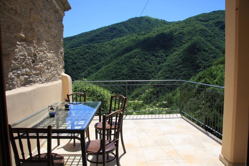 Vista desde la terraza a través del valle a las montañas enfrente de Rezzo