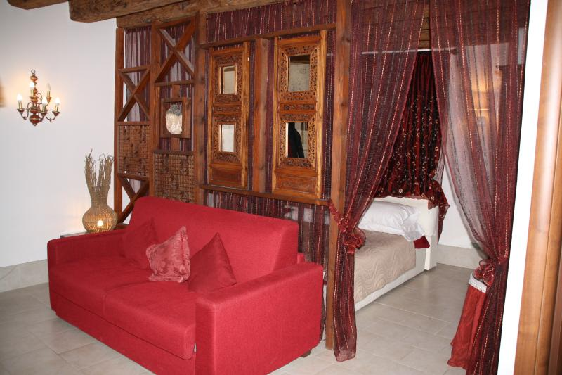 Living area with double sofa bed and sleeping area with double bed