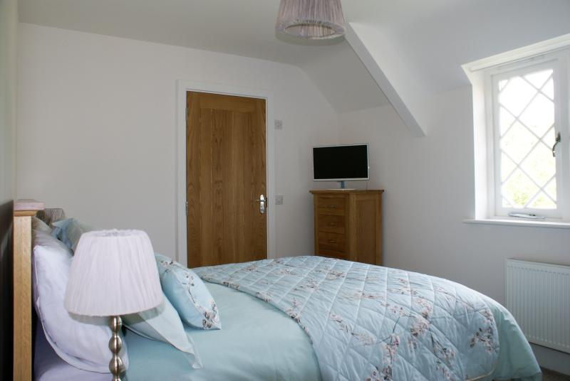Master Bedroom with ensuite shower room, Smart TV, fitted mirror-front wardrobes, plentiful storage.