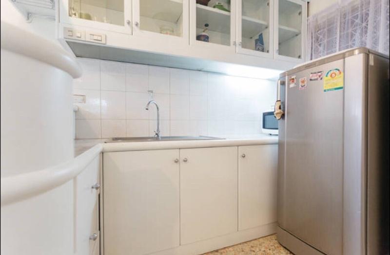Kleine pantry met koelkast, magnetron, bijkeuken