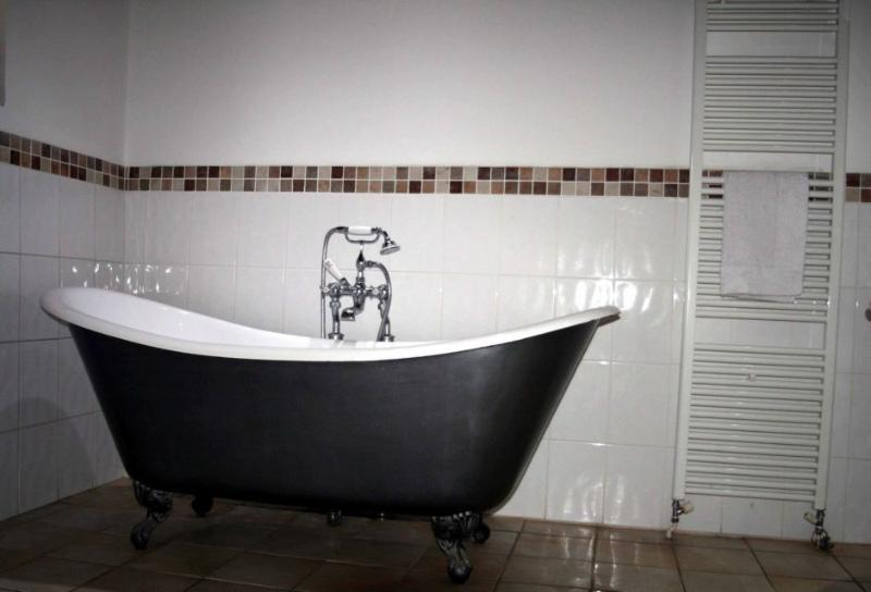 Period bathroom with large double ended roll top bath