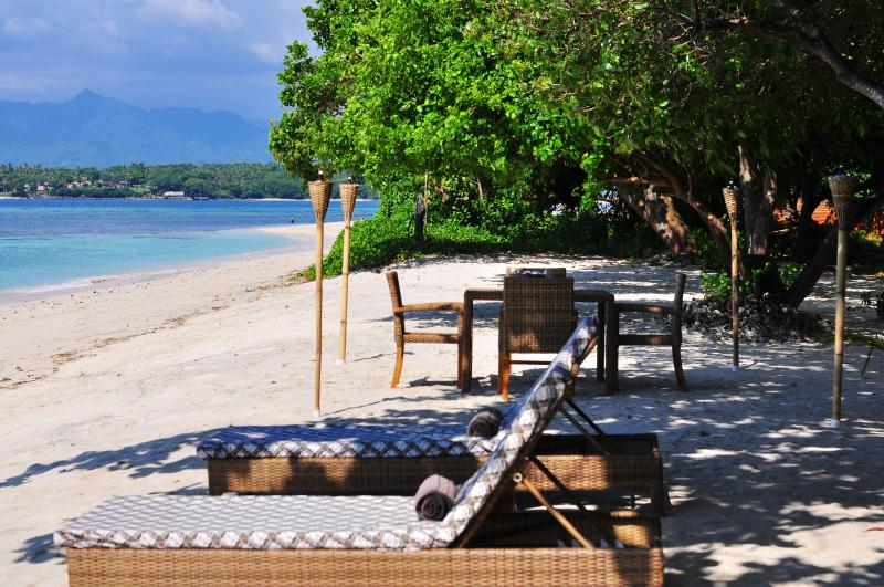 sun loungers and dining table at the private white sandy beach right in front of the villa