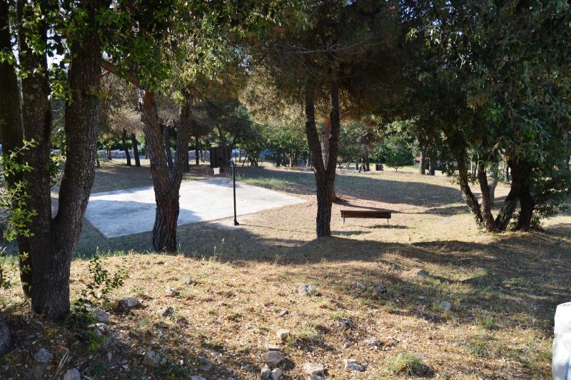 Zona verde con cancha de baloncesto, juegos infantiles y campo de futbol delante la casa