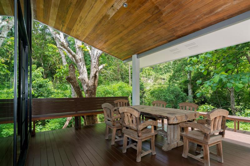 The deck is surrounded by coffee plants and massive trees.