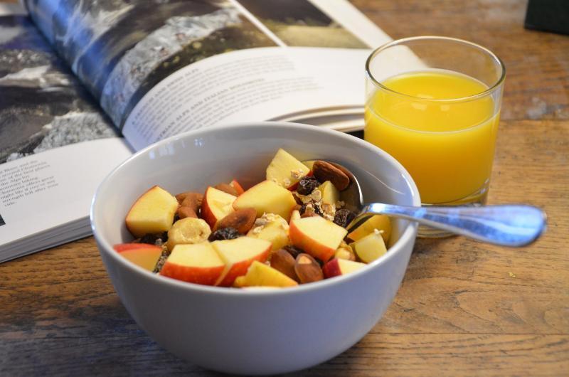Homemade organic meusli with fresh apple and organic orange juice