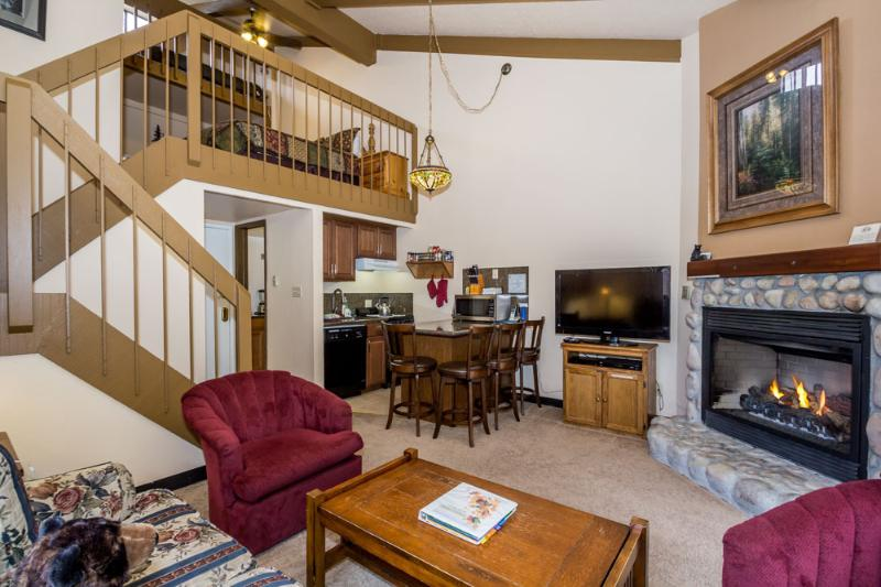 View of the living area with gas fireplace, sofa sleeper and kitchen/dining area and loft.