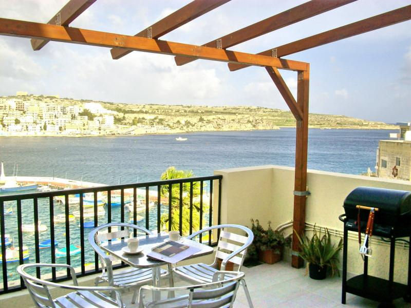 Winter Seafront view from terrace with garden furnitures, sunbeds and barbecue