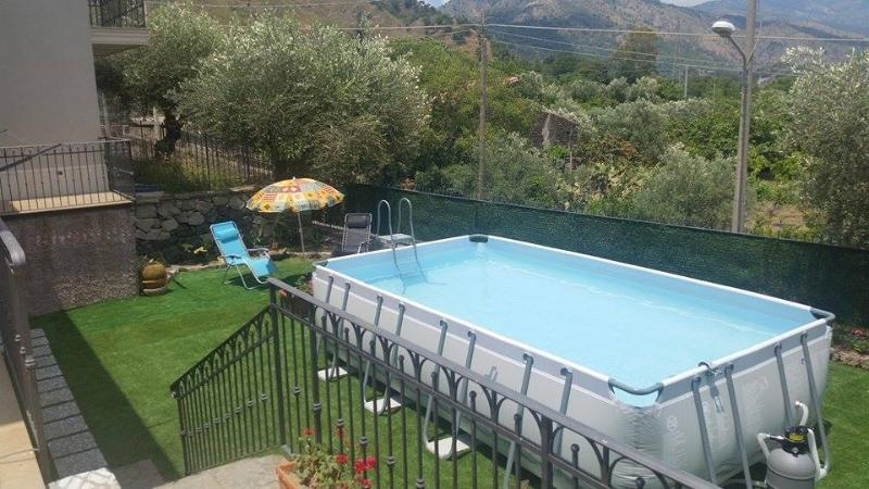 Giardinetto con erbetta, piscina, zona relax con ombrelloni e sdraio, tavolino con sedie, doccia