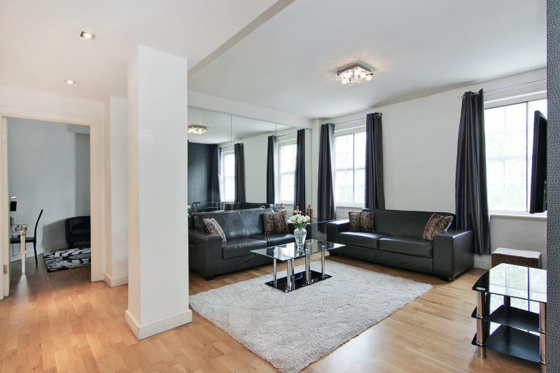 Luminosa e spaziosa, soggiorno con 2 grandi divani in pelle e tavolo da pranzo e sedie.