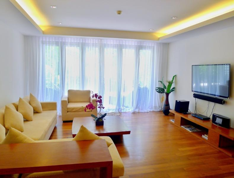 Comfortable sofa with arm chair, large TV with sound system in the living room
