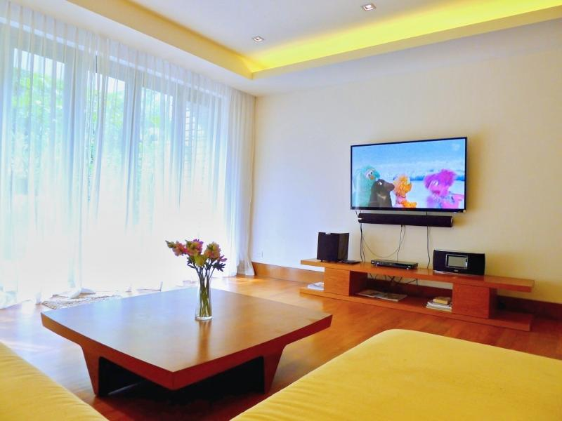 Spacious living area with a large flat screen TV, DVD and sound system