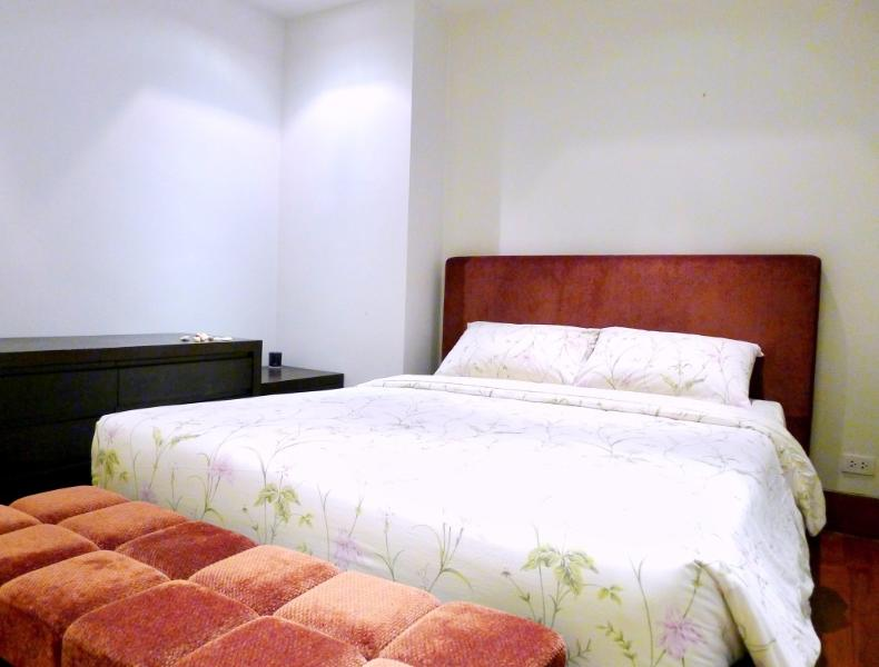 Guest bedroom with double bed, low closet and a couch