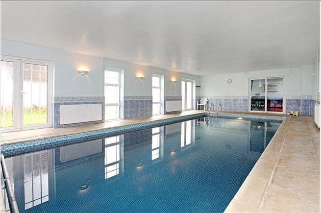 Heated indoor pool has french doors opening onto the rear garden .