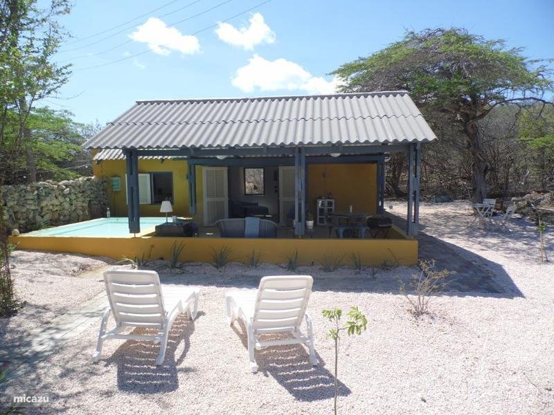 Aanzicht van uw appartement vanuit de royale tuin, compleet met zonnebedden en buitenmeubilair.