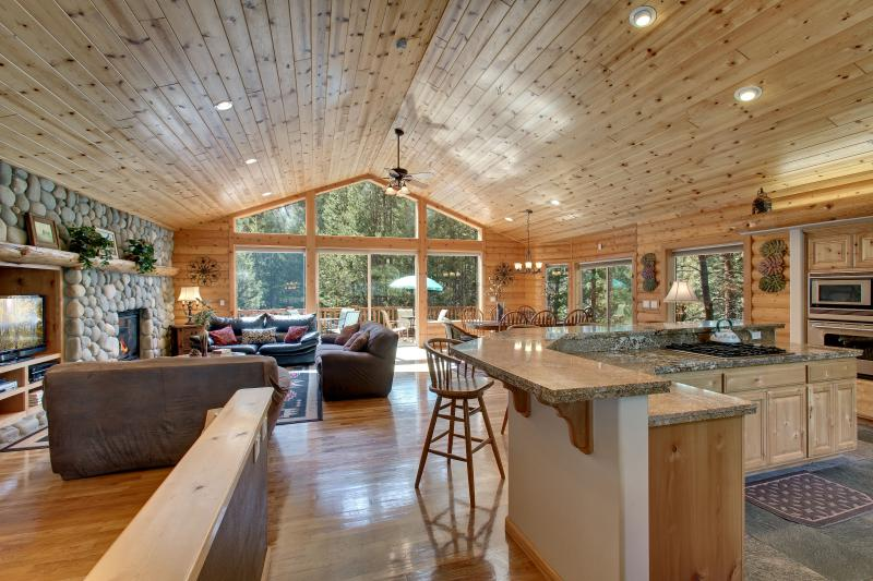 Living room with log interior, pine ceilings, oak hardwood floors and floor to ceiling windows