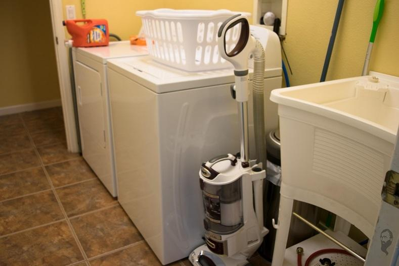 Indoor laundry room has full size washer and dryer and laundry tub.