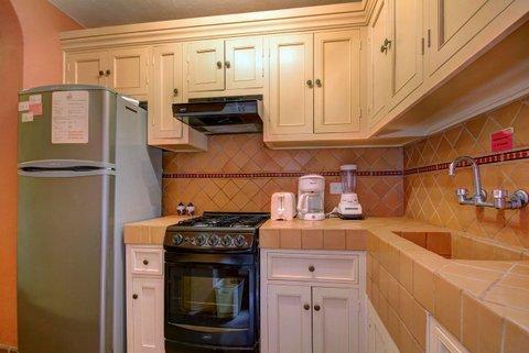 Kitchen with fridge, stove and basic appliances.