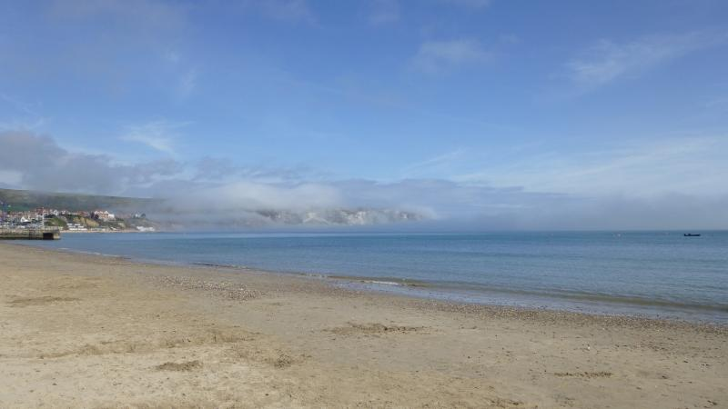 Early Spring sea mist clears letting the sun warm Swanage Beach.