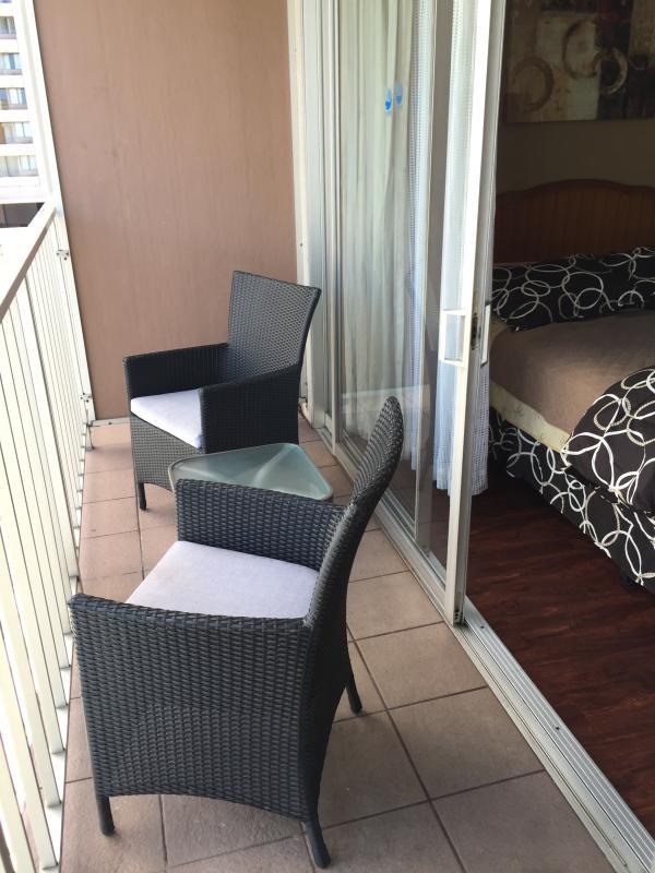 terraza al aire libre con 2 sillas y una mesa pequeña.