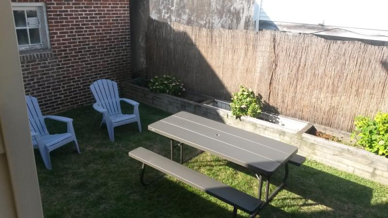 Comfortable Back Yard with Adirondack Chairs, Picnic Table and Propane BBQ Grill