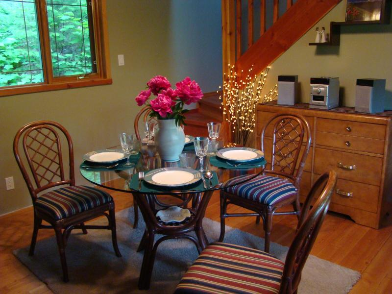 Dining room with a glass-top table for 4 plus a bench for 2 more, plus games and books