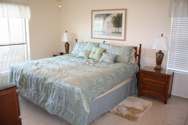 Master bedroom with flat panel TV, attached bathroom with double sinks, closet