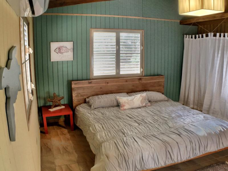 Master bedroom has a handcrafted king-size bed and air conditioner.