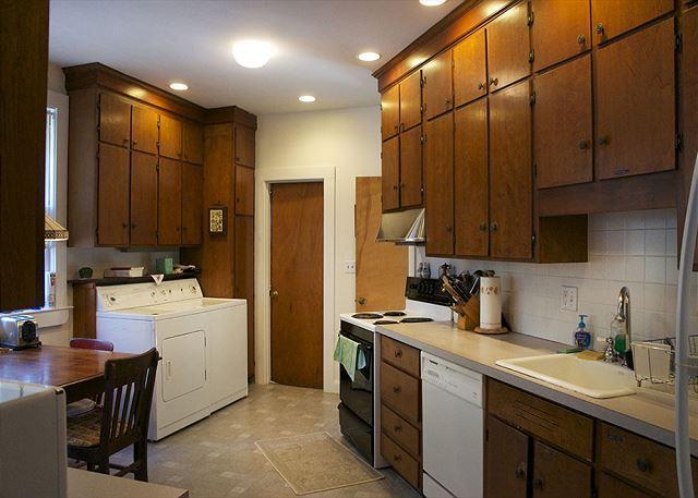 Gran cocina y comedor con máquinas de lavandería.