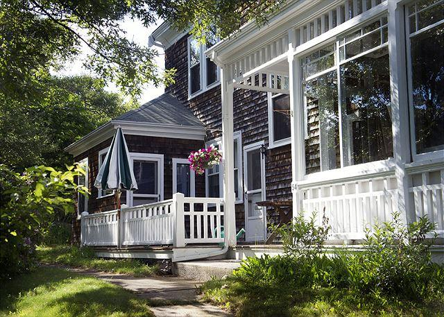 Side exterior porch with umbrella & seating/dining area.