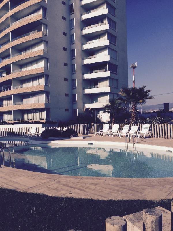 departamento con una linda vista panoramica de la playa y piscina.