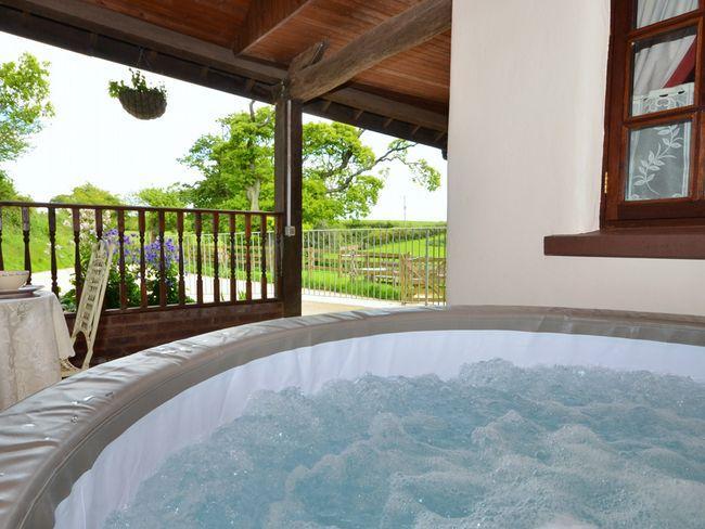 zona cubierta en la parte delantera de la propiedad con bañera de hidromasaje