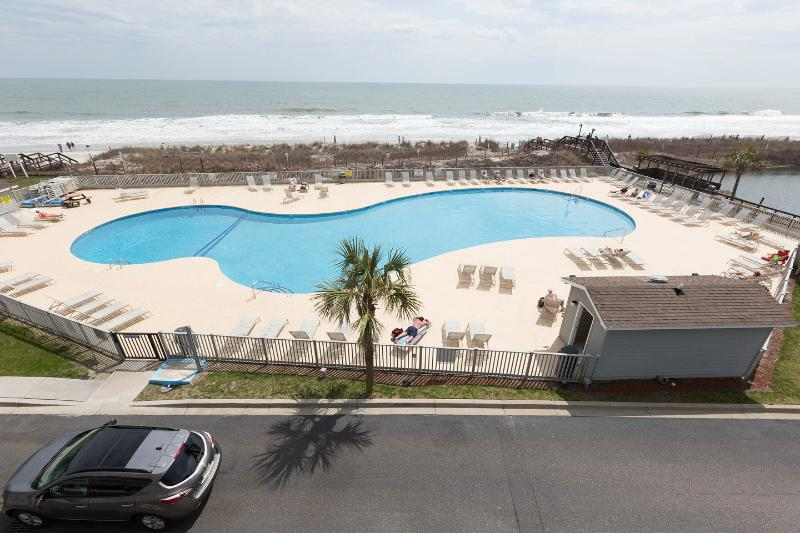 Condo overlooks oceanfront pool.
