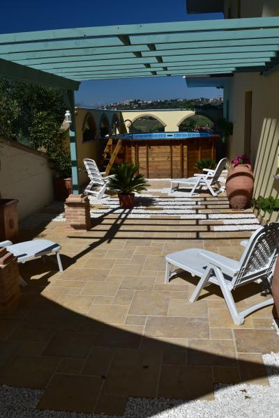 patio cerrado con piscina, estanque, barbacoa, mesa y área sombreada parcialmente con tumbonas.
