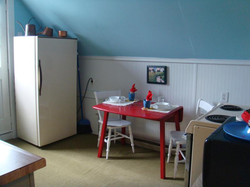 Kitchen with refrigerator, table, 2 chairs, and stove/oven.