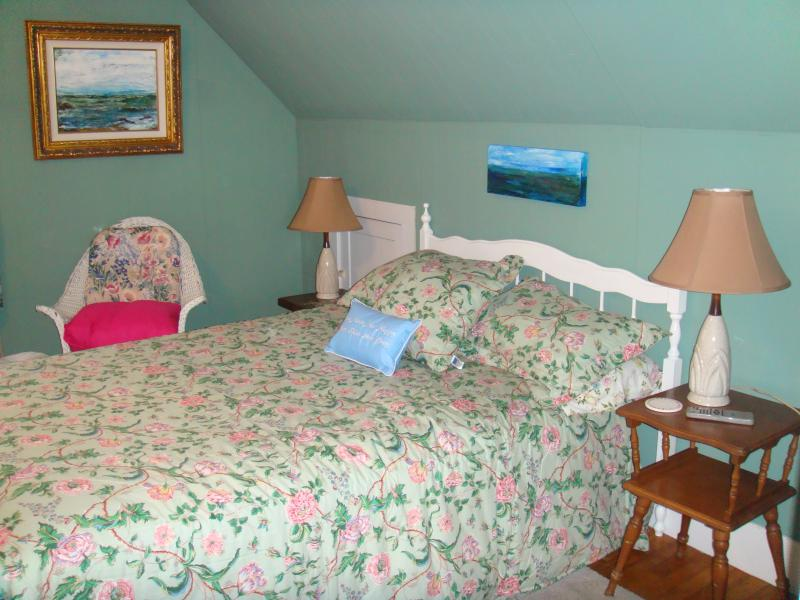 Another photo - Bedroom with 2 lamp stands and wicker side chair.