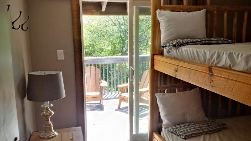 Rustic log bunks with private exit to upper deck, sleeps 4.