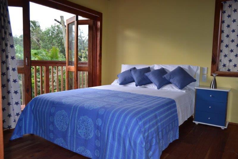 sala de jardín configurado con cama de matrimonio, sobre la papaya, limón, naranja, higueras y las hierbas del jardín.