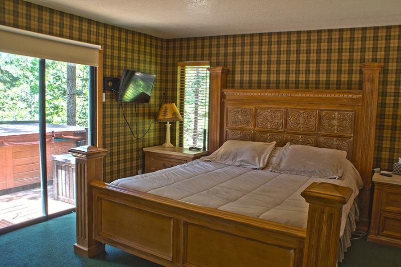 Master bedroom with sliding door leading to the hot tub and deck over the river.
