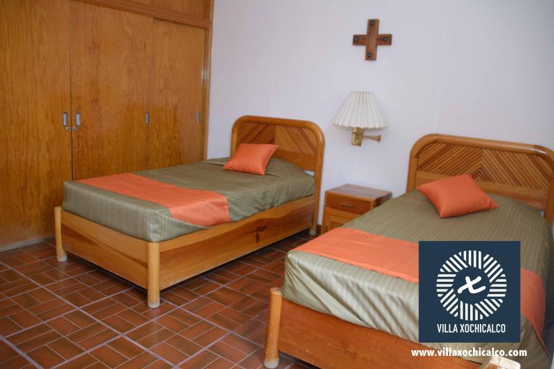 Habitación con dos camas individuales en la planta baja compartiendo baño con otra habitación.
