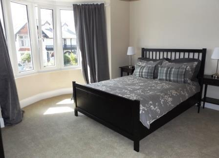 Comfortable master bedroom with double bed, bedside units and reading lamps.