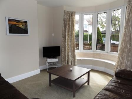 Comfortable lounge with beautiful bay window. TV for guests to relax and enjoy.