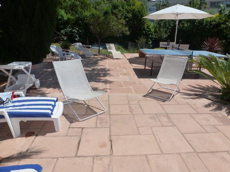 grande terrasse avec fauteuils de piscine