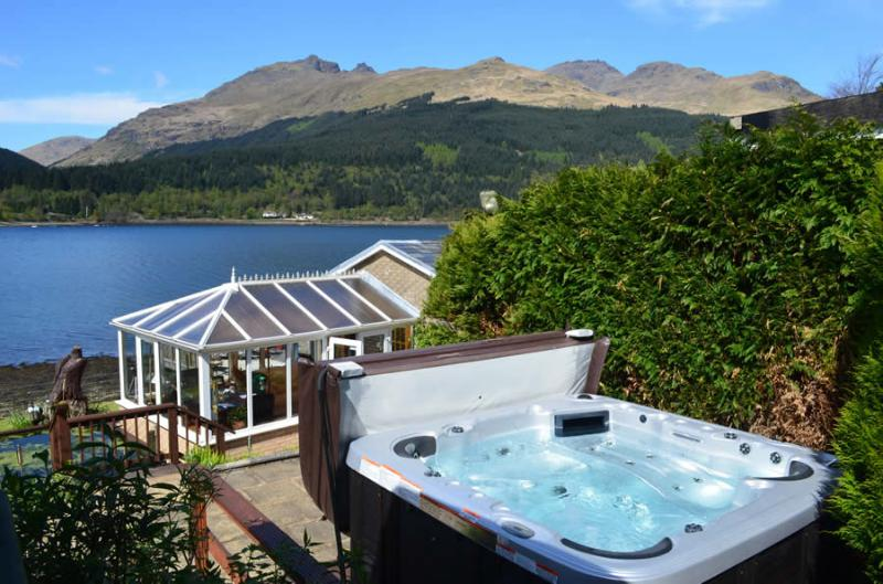Deck area overlooking Loch Long, direct beach access ! use of boat for fishing & Private Hot Tub !