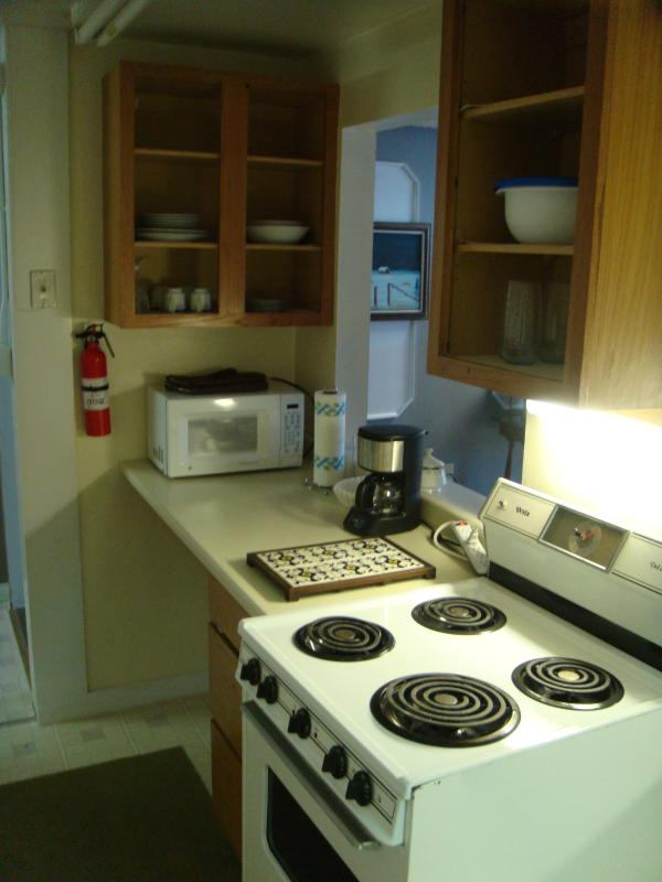 Kitchen with stove, microwave, coffee pot, espresso machine, toaster, pots/pans, dishes