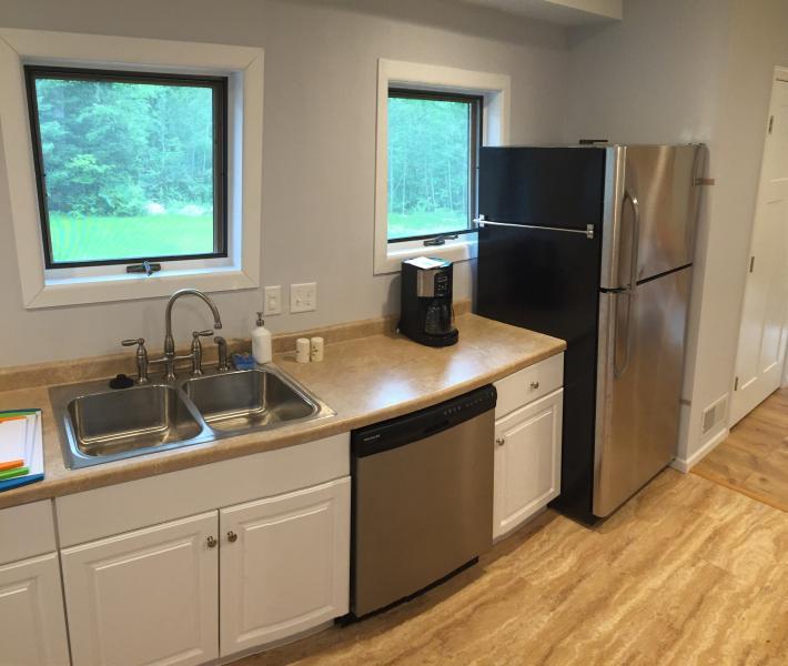 Keuken met alle nieuwe roestvrijstalen apparaten - op zoek naar de achtertuin en Plum onder Woods