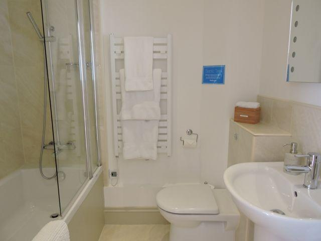 The downstairs bathroom has a toilet, wash basin and comfortable bath with shower over